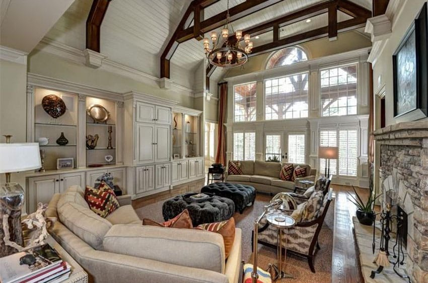 Traditional living room with cream custom cabinets high ceiling and wrought iron chandelier