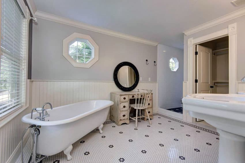 Traditional master bathroom with roll top soaking bathtub and mosaic tile penny tile