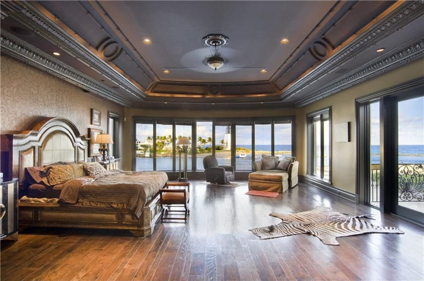 Traditional master bedroom with expansive ocean views carmel oak wood flooring and tray ceiling