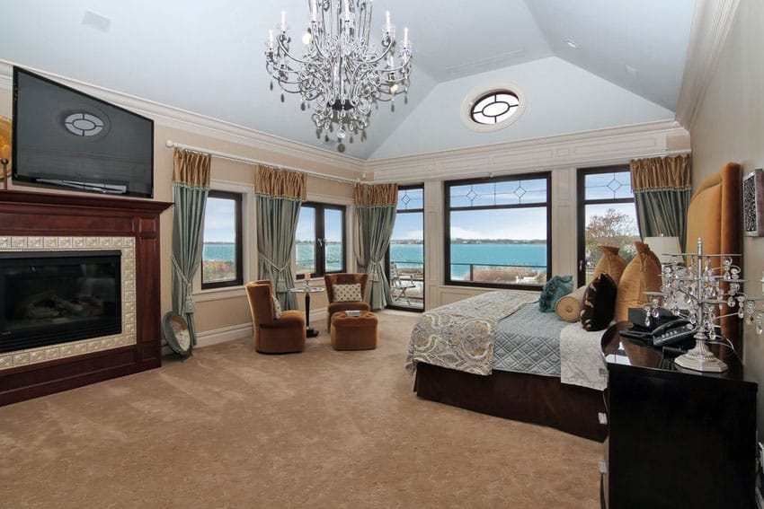 Traditional master bedroom with lake views and gas fireplace