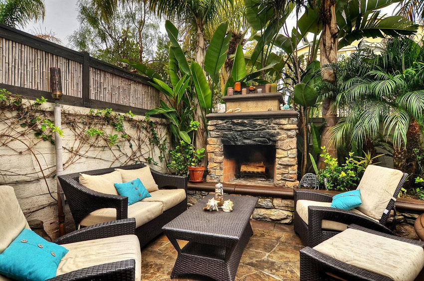 Tropical patio with fireplace palms and bamboo fence