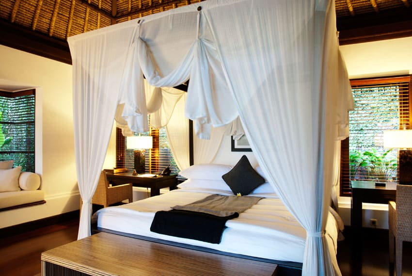 Tropical style bedroom with four post bed and curtains