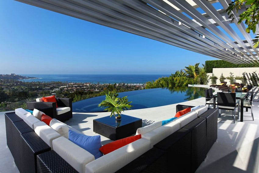 Upscale patio with ocean views facing infinity pool