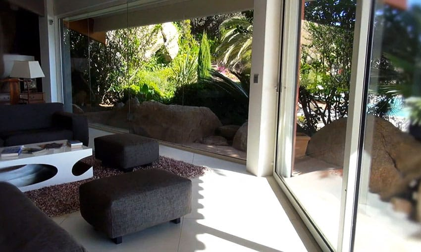 View of garden from living room through large glass windows