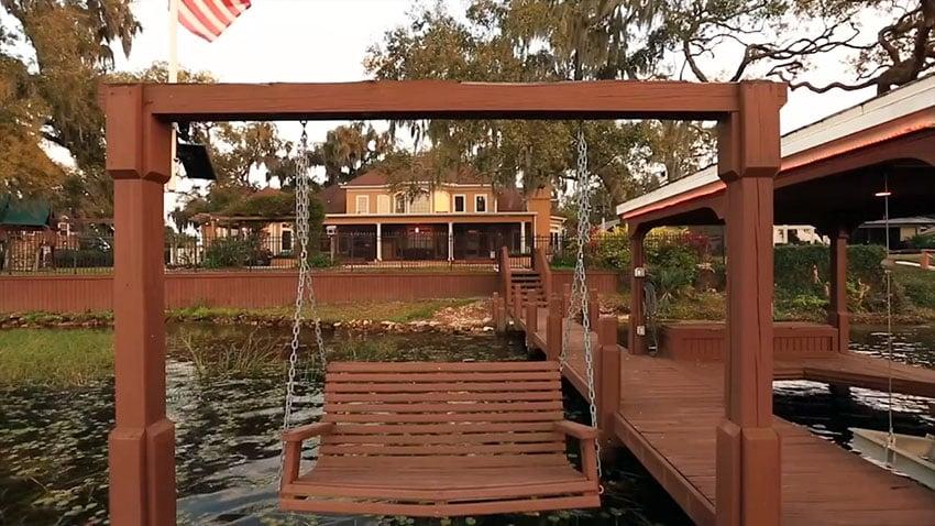 Wooden swinging bench on lake dock
