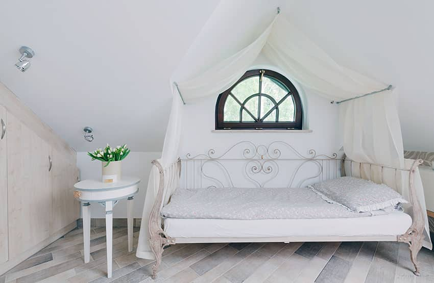 Attic bedroom with white canopy curtain over bed