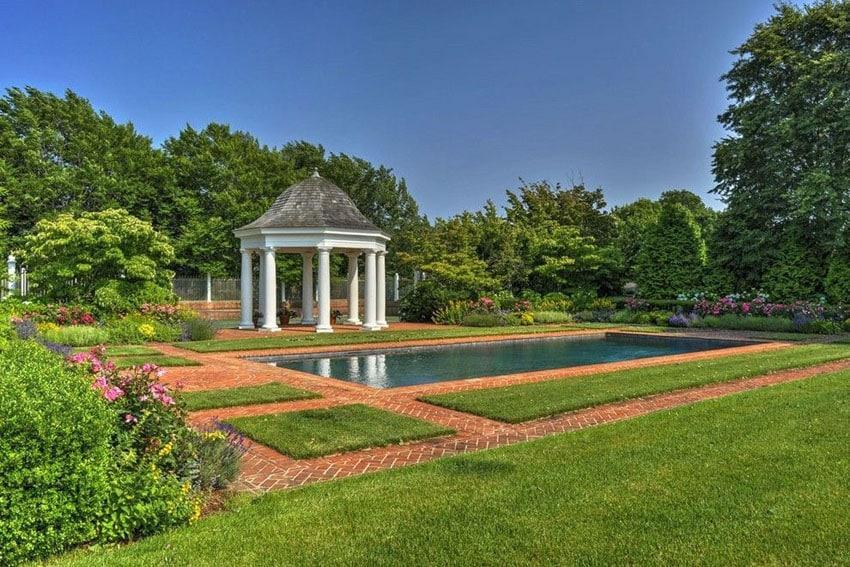 Backyard garden pool next to brick path and pillar gazebo