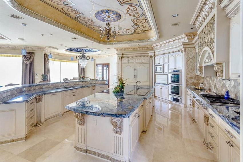 Beautiful Mediterranean kitchen with decorative molded cabinetry, jewel tone granite counters and chandelier