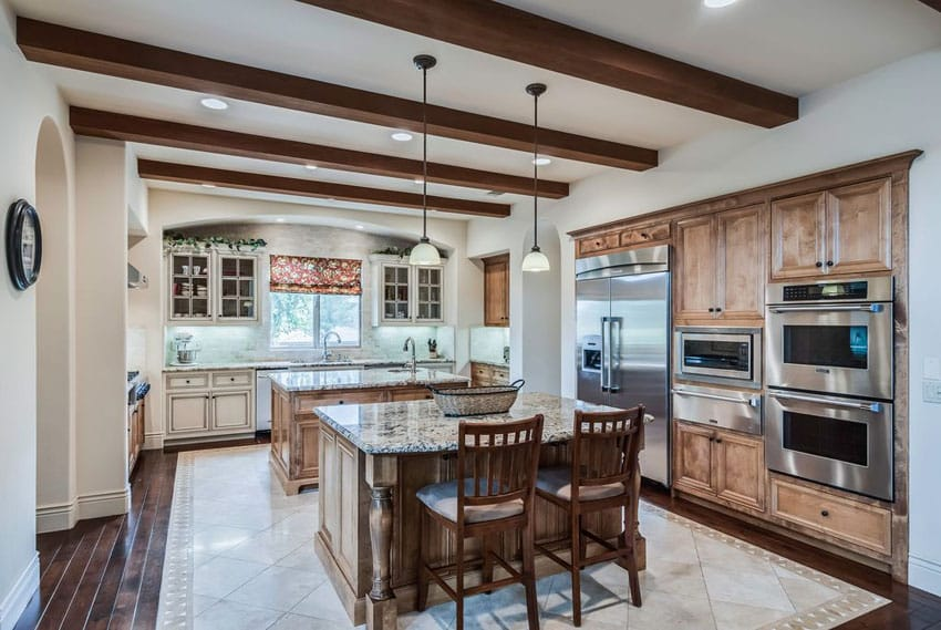 Beautiful traditional kitchen with two islands, decorative woodwork, exposed beam ceiling and wood plank floors