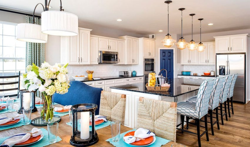 Beautifully decorated traditional kitchen with white cabinets, blue pearl silver granite counters and open dining area