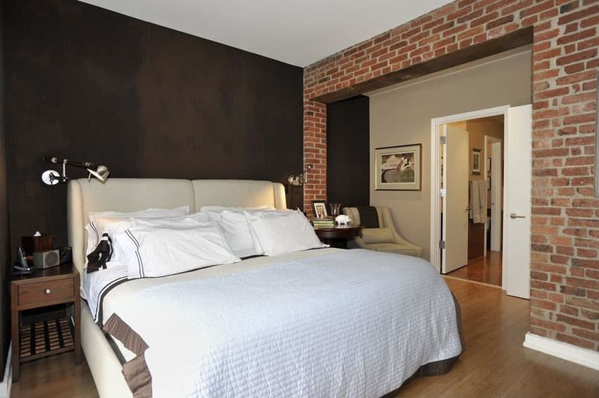 Bedroom with black painted walls and brick wall