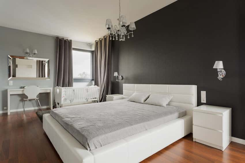 Bedroom with solid black walls, white bed, chandelier and wood floors