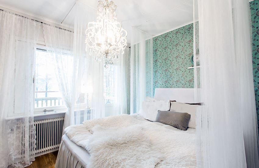 Bedroom with white sheer curtains, white bed throw, elegant chandelier and vintage patterned wallpaper