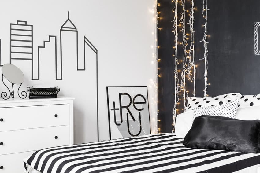 Black and white bedroom with matching bed cover and hanging lights