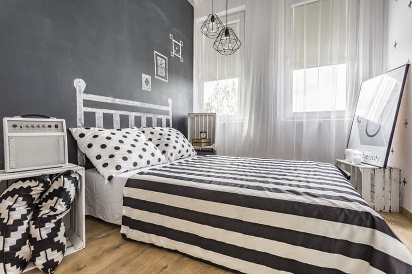 Black and white decor bedroom with chalkboard wall and hanging Edison lamps