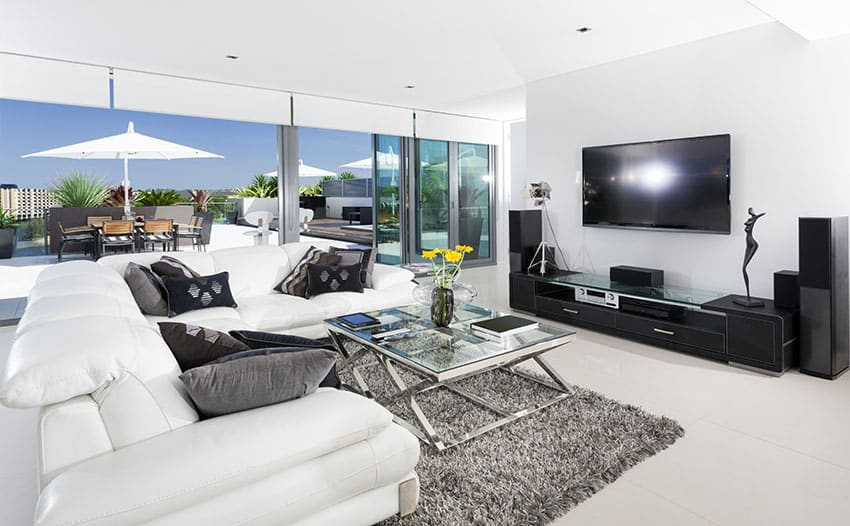 Clean white living room with black entertainment center and large sliding doors to outdoor rooftop patio