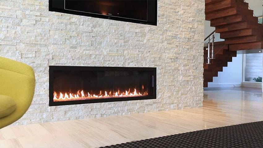 Close up view of modern gas fireplace in stone wall