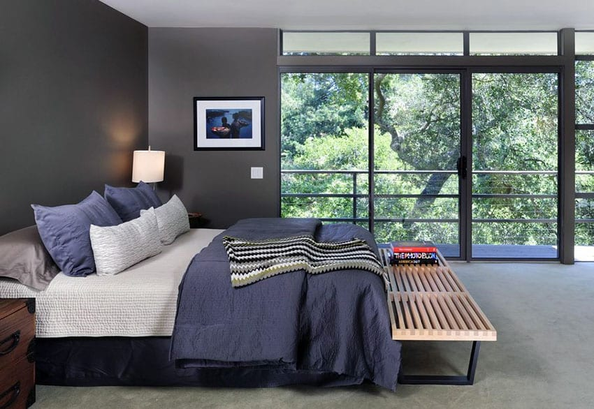 Contemporary bedroom with dark walls and wrap around outside views