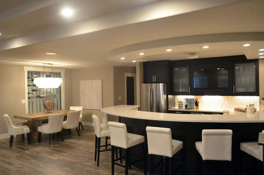 Contemporary kitchen with arctic white quartz counter and curved dining peninsula with white bar stools