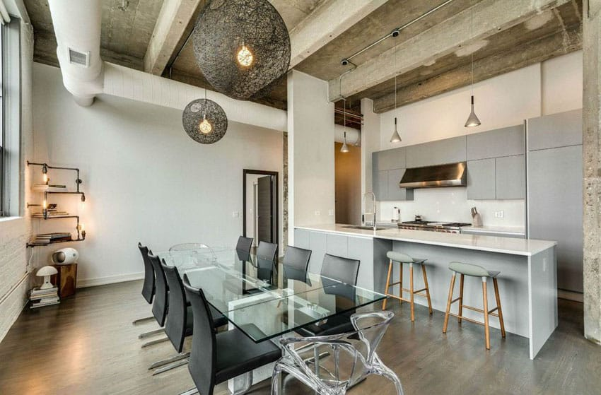 Contemporary kitchen with industrial design, gray cabinets and white counter peninsula with glass dining table