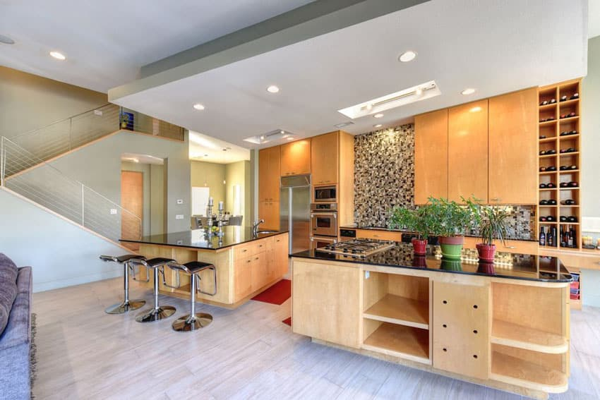 Contemporary kitchen with light color cabinets and two islands, one for dining and one for food prep
