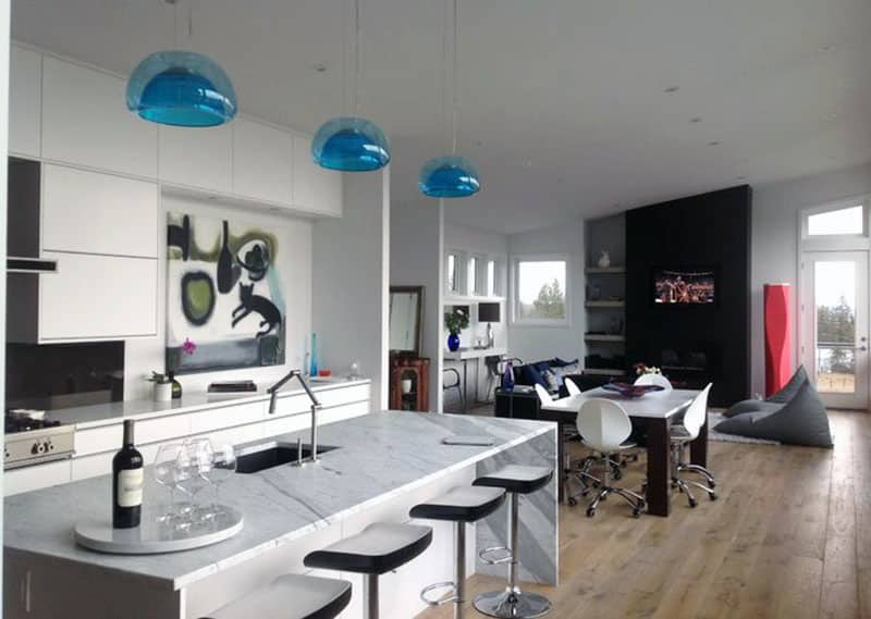 Contemporary kitchen with marble island and adjustable swivel barstools and blue glass pendant lights