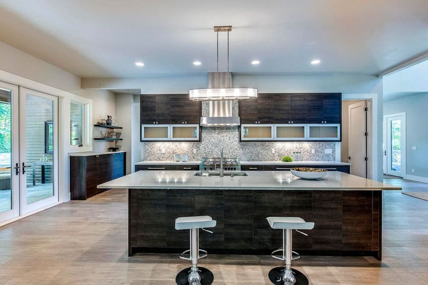 Contemporary kitchen with meridian gray quartz counter island with chrome bar stools and brushed beige marble tile floors