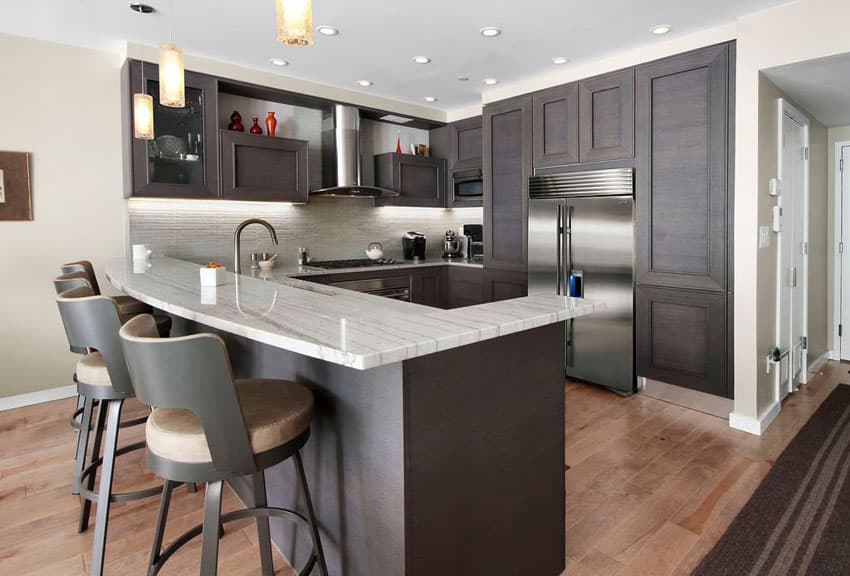 Contemporary kitchen with peninsula dark cabinets and mini pendant lights
