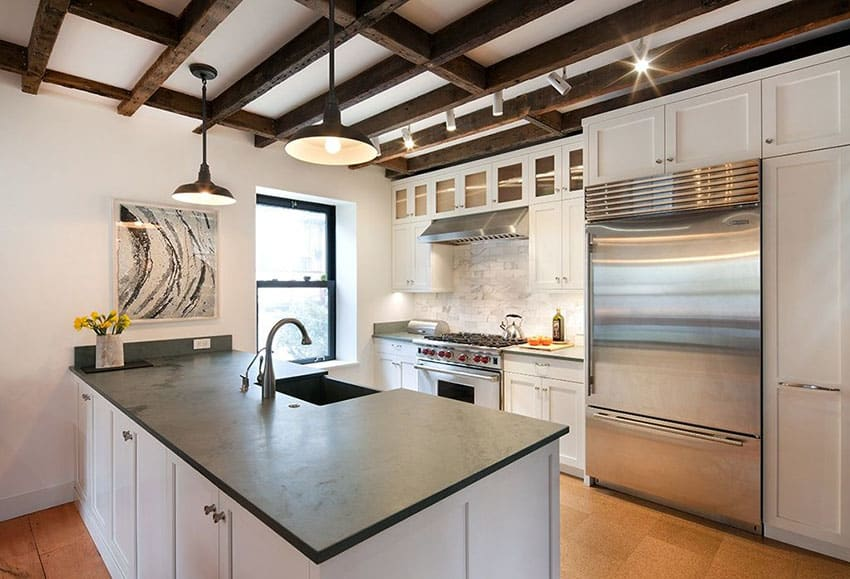 Contemporary kitchen with peninsula soapstone counters, exposed beams and white shaker cabinets