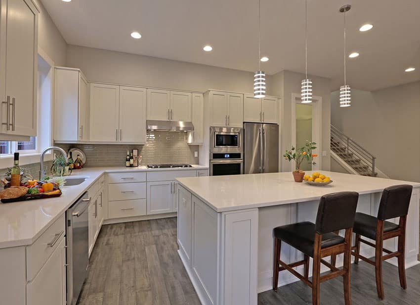 Contemporary kitchen with white cabinetry, wood flooring and aluminum mini pendant lights