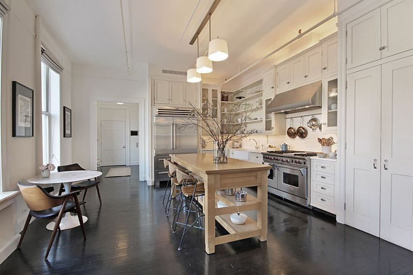 Contemporary kitchen with white cabinets and portable wood island