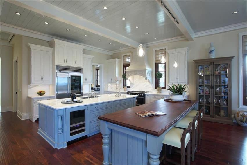 Cottage style kitchen with two light blue painted islands with carrara marble and wood countertop