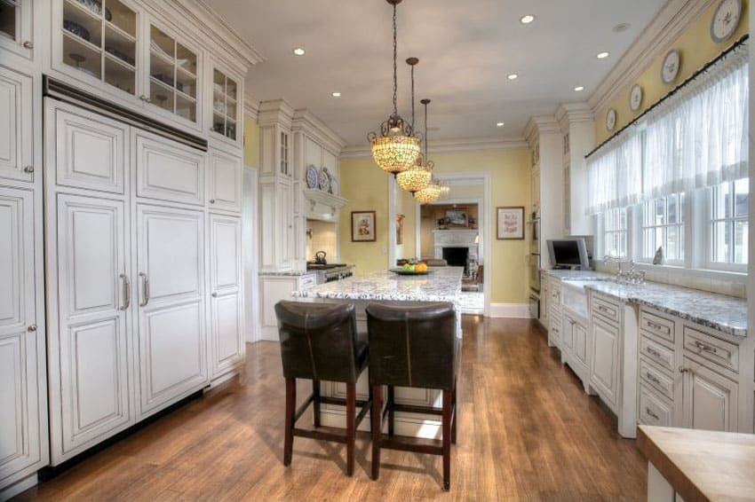 Country kitchen with white cabinets and hidden freezer fridge with breakfast bar island and white granite counters