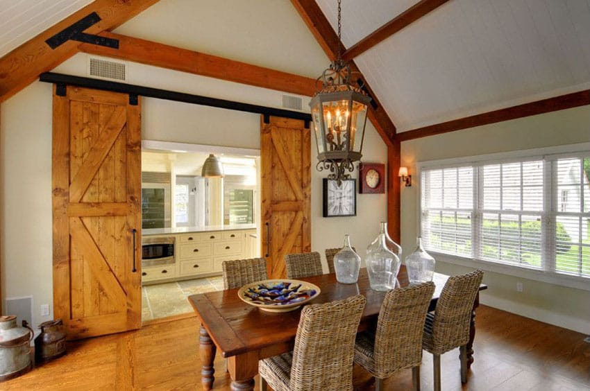 Country style dining room with vaulted ceiling and sliding barn doors