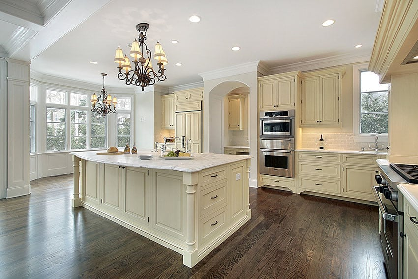 Cream color cabinet kitchen with marble counter, large island and wood floors