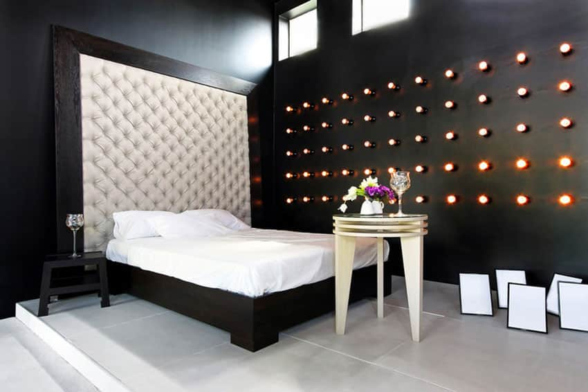 Custom designed black bedroom with rows of wall lights and tufted headboard