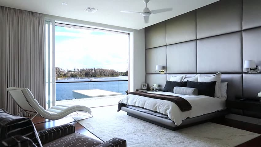 Custom designed modern master bedroom with lake views and lounge chair