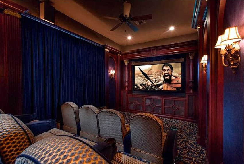 Custom home movie room with decorative wood theater seats and wall sconce lighting