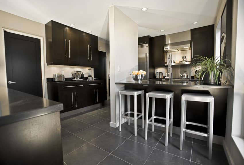 Dark cabinet contemporary kitchen with solid surface counter dining peninsula and porcelain floor tiles