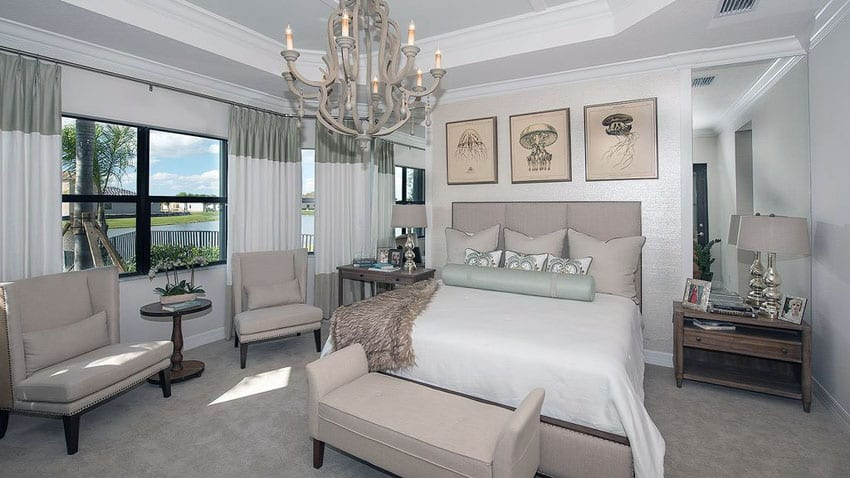 Decorated bedroom with contemporary chandelier and tray ceiling