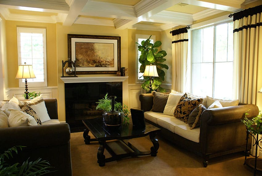 Decorated formal yellow living room with coffered box ceiling