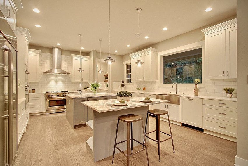 Double island transitional kitchen with calacatta gold marble countertops and white cabinets