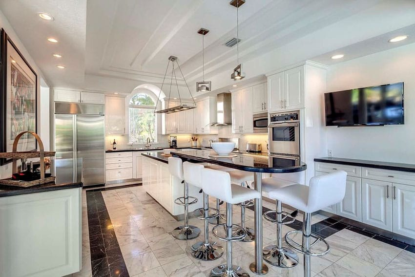 Eclectic kitchen with white cabinets and breakfast bar island with black granite counters