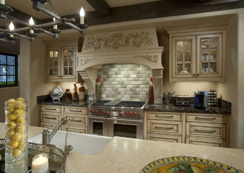 Elegant kitchen with cream cabinets with raised panel design and decorative oven hood