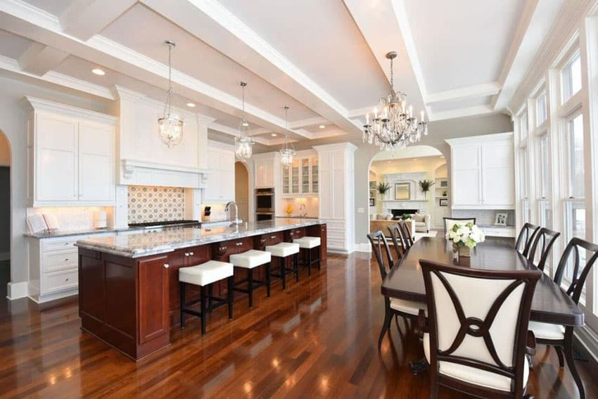 Elegant traditional kitchen with large rectangular island with backless leather counter stools