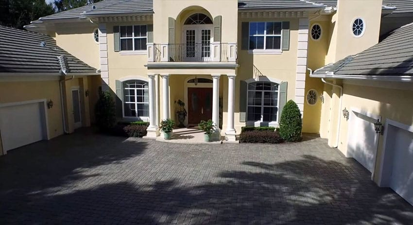 Front driveway to luxury Florida house with colonnade entry and front second story balcony