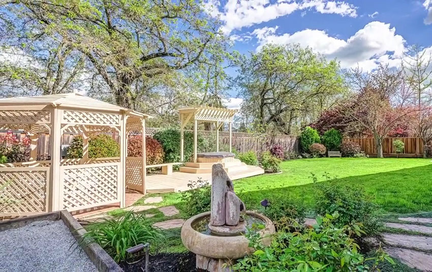 Gazebo and pergola in backyard with stepping stone path and water fountain