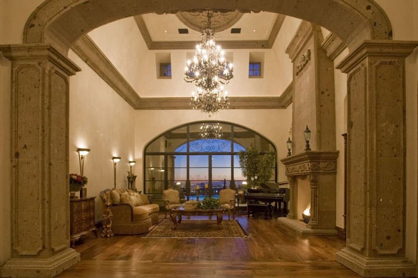 Grand living room with stone pillars archways, high ceiling and chandelier
