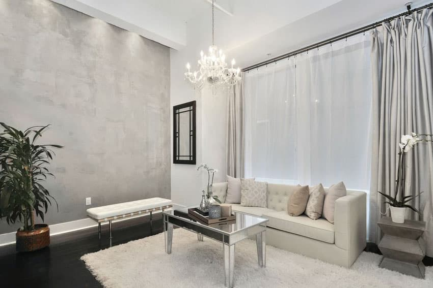Gray and white living room with shag area rug, curtains, sofa and chandelier