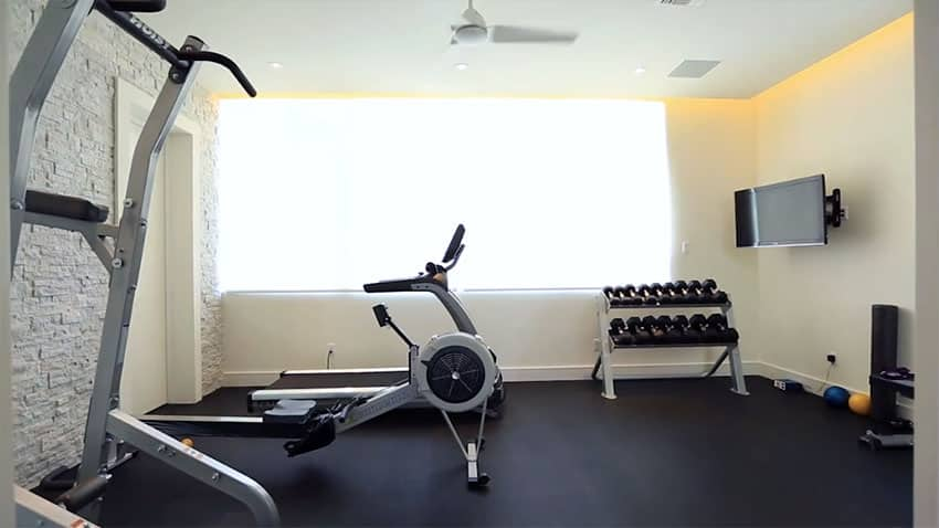 Home gym workout room with exercise machines and mat floors